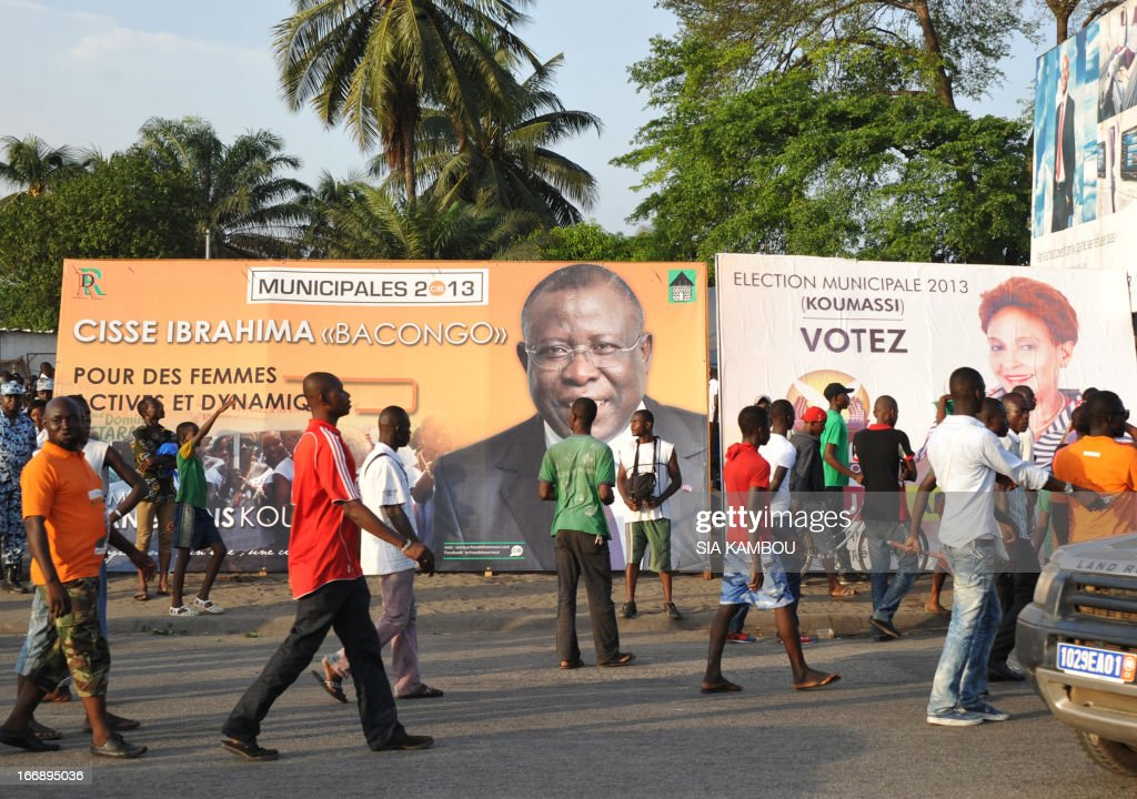 A picture taken on April 11, 2013 in the Koumassi district of Abidjan shows people walking past posters of candidates for the April 21 local elections. The party of Ivorian President Alassane Ouattara on April 17, 2013 voiced concern over growing political tension ahead of local polls meant to cement post-conflict stabilisation.