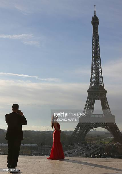A picture taken on April 12 2016 at the trocadero in Paris shows a woman posing in front of the Eiffel tower at sunrise / AFP / LUDOVIC MARIN