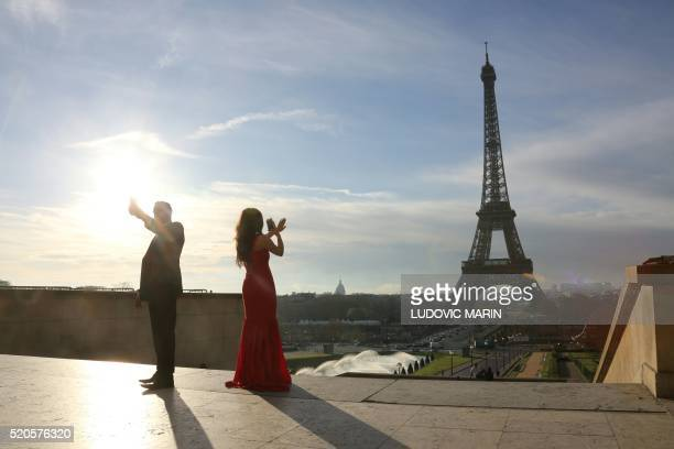 A picture taken on April 12 2016 at the trocadero in Paris shows a couple taking pictures of the Eiffel tower at sunrise / AFP / LUDOVIC MARIN