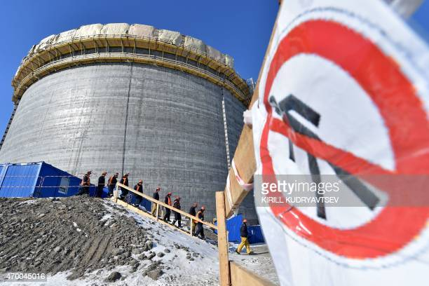 A picture taken on April 16 2015 shows workers walking past a natural gas reservoir at the port of Sabetta in the Kara Sea shore line on the Yamal...