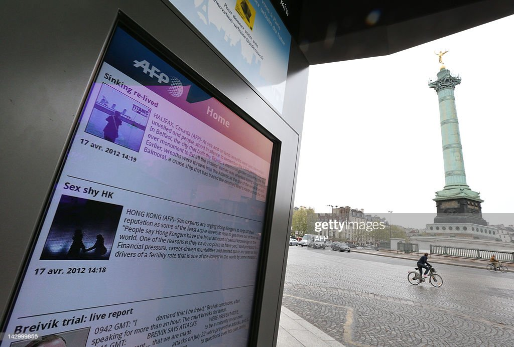 A picture taken on April 17, 2012 shows a screen of the 'Concept Abribus' bus shelter on the Bastille Square in Paris, by France's JC Decaux, the biggest outdoor advertising group in Europe and Asia. Since March 20, 2012, pedestrians can read national and international news by Agence France-Presse (AFP) on outdoor rolling screens and interactive applications in French and English.