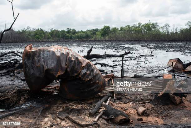A picture taken on April 19 2017 shows a destroyed cooking tank at an illegal oil refinery site in the Niger Delta region near the city of Warri NNS...