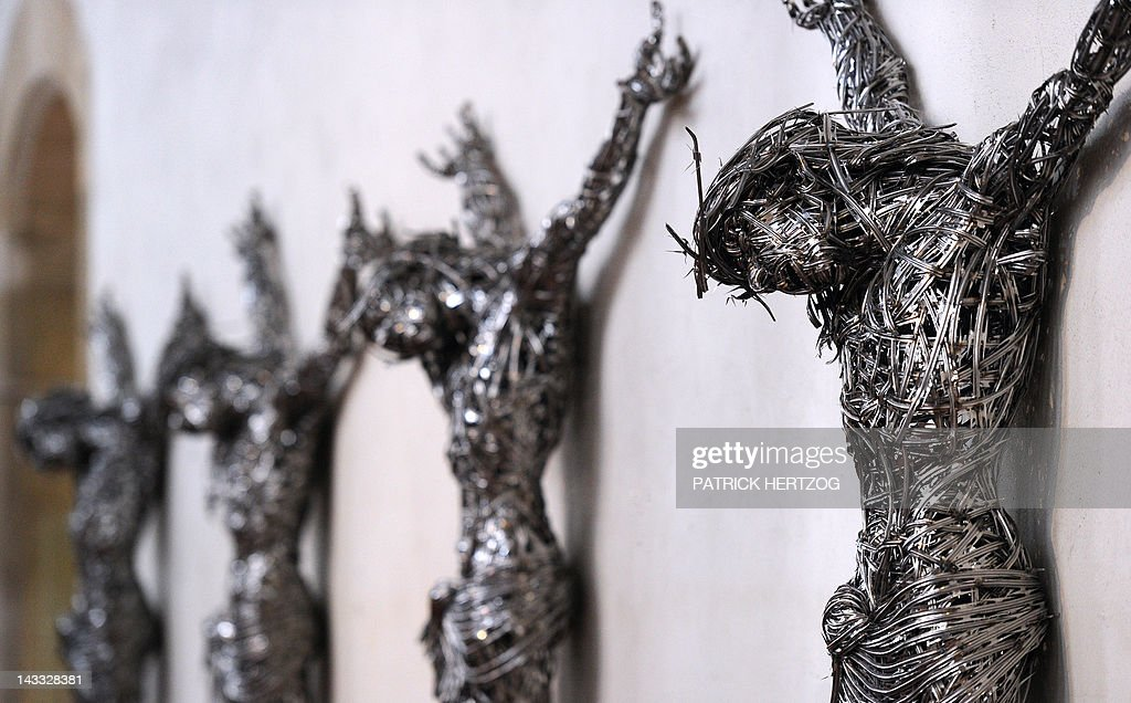 A picture taken on April 24, 2012 shows contemporary sculptures untitled 'Decor' by Algerian artist Adel Abdessemed on April 24, 2012 at the chapel of the Unterlinden museum in the northeastern French city of Colmar, exhibited besides the 'Isenheim Altarpiece' (aka 'retable d'Issenheim' in French) by German Renaissance painter Matthias Grunewald, as part of the 500-year anniversary of this famed Renaissance religious work. Abdessemed borrowed the image of Christ crucified from Mattias Grünewald to create four crucified Christ, laced with industrial grade razor wire. His work will be shown for the first time in Europe from April 27 to September 16, 2012 in Colmar.