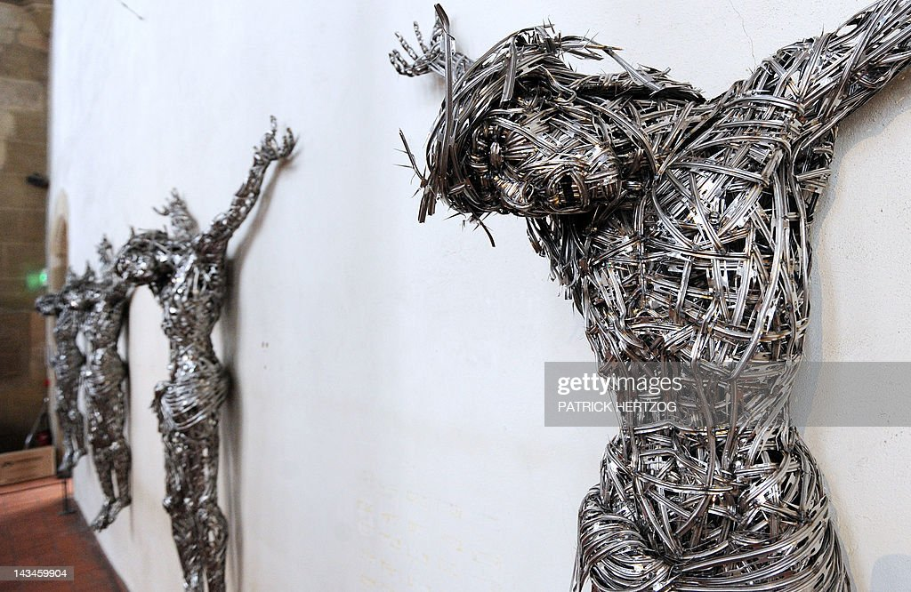 A picture taken on April 24, 2012 shows contemporary sculptures untitled 'Decor' by Algerian artist Adel Abdessemed on April 24, 2012 at the chapel of the Unterlinden museum in the northeastern French city of Colmar, exhibited besides the 'Isenheim Altarpiece' (aka 'retable d'Issenheim' in French) by German Renaissance painter Matthias Grunewald, as part of the 500-year anniversary of this famed Renaissance religious work. Abdessemed borrowed the image of Christ crucified from Mattias Grünewald to create four crucified Christ, laced with industrial grade razor wire. His work will be shown for the first time in Europe from April 27 to September 16, 2012 in Colmar. AFP PHOTO / PATRICK HERTZOG