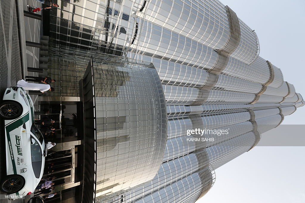 A picture taken on April 25, 2013 shows a Ferrari police vehicle at the foot of the Burj Khalifa tower in the Gulf emirate of Dubai. Two weeks after introducing the Lamborghini police car, Dubai Police has introduced a Ferrari to the fleet, to further strengthen the 'image of luxury and prosperity' of the emirate. AFP PHOTO / KARIM