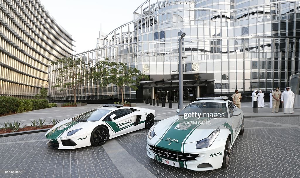 A picture taken on April 25, 2013 shows Lamborghini and Ferrari police vehicles at the foot of the Burj Khalifa tower in the Gulf emirate of Dubai. Two weeks after introducing the Lamborghini police car, Dubai Police has introduced a Ferrari to the fleet, to further strengthen the 'image of luxury and prosperity' of the emirate. AFP PHOTO / KARIM