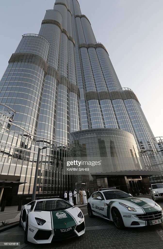 A picture taken on April 25, 2013 shows Lamborghini (L) and Ferrari police vehicles at the foot of the Burj Khalifa tower in the Gulf emirate of Dubai. Two weeks after introducing the Lamborghini police car, Dubai Police has introduced a Ferrari to the fleet, to further strengthen the 'image of luxury and prosperity' of the emirate. AFP PHOTO / KARIM