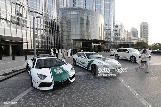 A picture taken on April 25 2013 shows Lamborghini and Ferrari police vehicles at the foot of the Burj Khalifa tower in the Gulf emirate of Dubai Two...