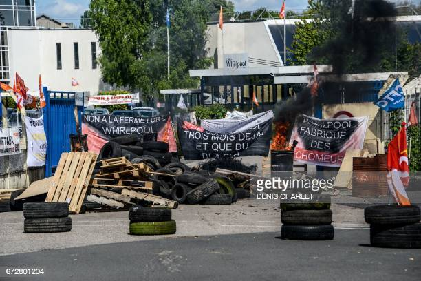 A picture taken on April 25 2017 shows tires and banners displayed outside the US appliance manufacturer Whirlpool factory in Amiens northern France...