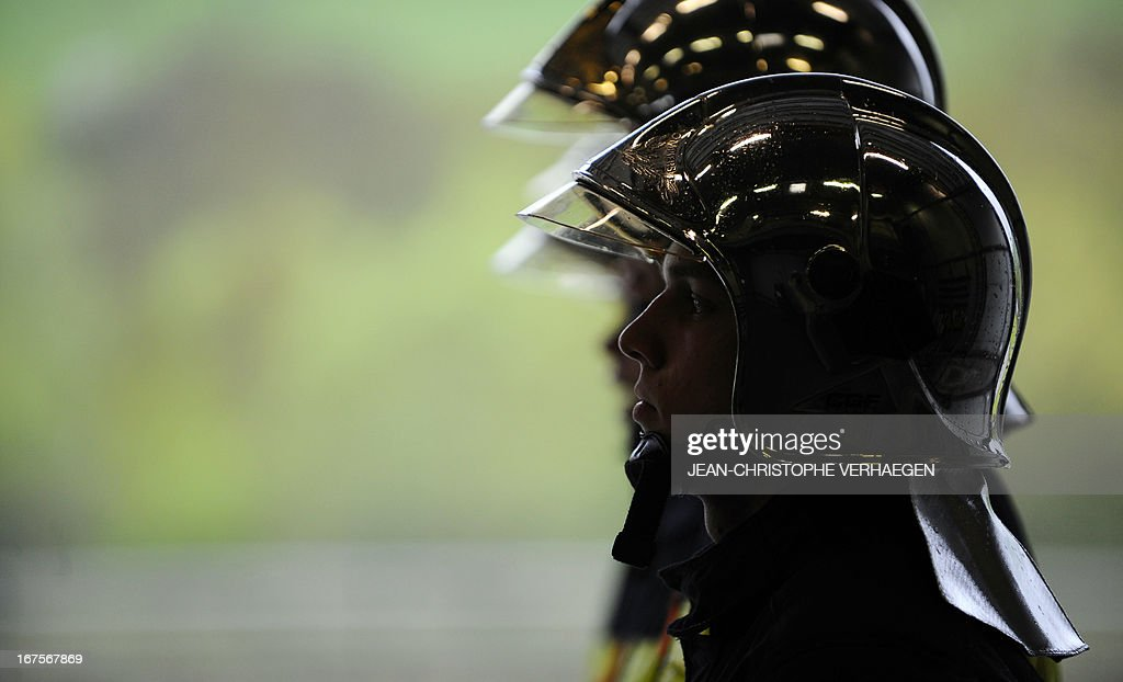 A picture taken on April 26, 2013 shows firemen wearing helmets as they stand at attention at the firehouse of Neuves-Maisons, eastern France.