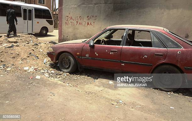 A picture taken on April 26 2016 shows a boy walkwing past a bullet riddled car and a wall with an inscription about Ibrahim Zakzaky the leader of...