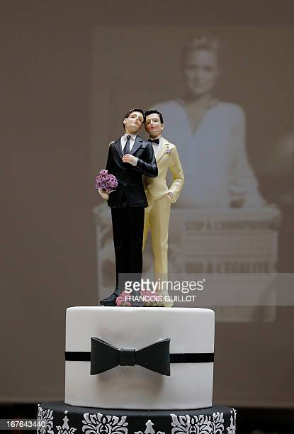 Picture taken on April 27 2013 in Paris shows plastic figurines of two men displayed on a fake cake displayed at the Gay marriage fair in Paris The...