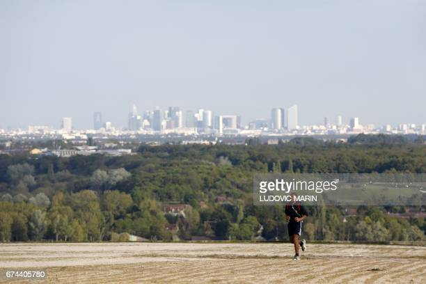 A picture taken on April 27 2017 from a station of the 'Axe majeur' in Cergy Pontoise outside Paris shows a jogger in front of skyscrapers in the...