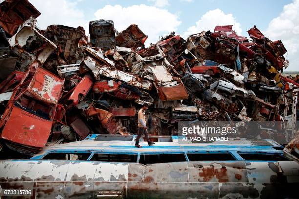 TOPSHOT A picture taken on April 3 shows a man walking amidst wrecked vehicles some had been previously used as barricades piled in a junkyard in...
