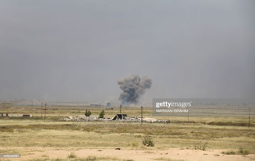 A picture taken on April 30, 2016 shows smoke billowing in the town of al-Bashir, south of the city of Kirkuk, as Iraqi pro-government forces, Shiite fighters from the Popular Mobilisation units, and allied paramilitaries launch an operation to retake it from the Islamic State group (IS). The jihadist group (IS) fired rockets suspected of carrying a mustard agent last month from Bashir on Taza Khurmatu, another town in the northern province of Kirkuk where attack killed three children, wounded a large number of people and pushed thousands more to flee Taza out of fear that it would be repeated. IS overran large areas north and west of Baghdad in 2014, but has since lost significant ground to Iraqi forces backed by US-led air strikes and training. / AFP / Marwan IBRAHIM