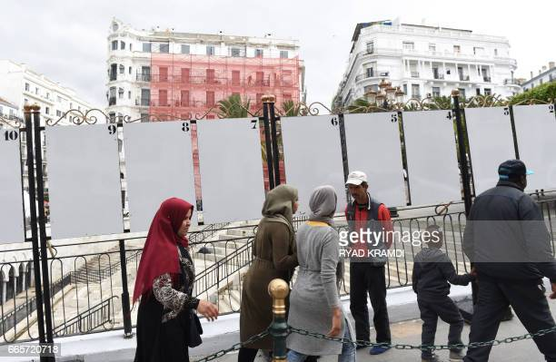A picture taken on April 6 2017 in the Algerian capital Algiers shows passersby walking past blank displays yet to be filled by candidates competing...