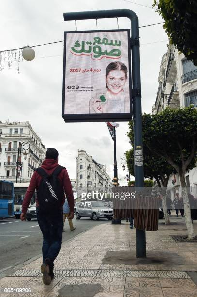 A picture taken on April 6 2017 shows an illuminated billboard with the slogan 'make your voice heard' written in Arabic as pedestrians walk along a...