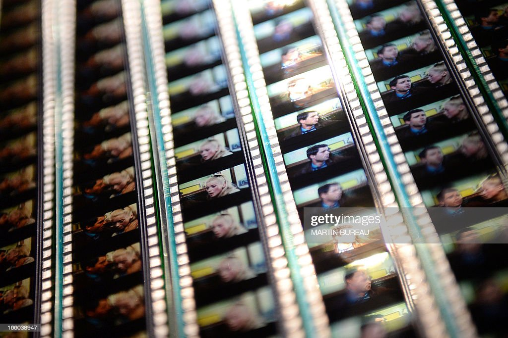 A picture taken on April 8, 2013 at the Cinematheque Francaise in Paris shows frames of a film reel presented during the retrospective exhibition dedicated to French movie director Jacques Demy. AFP PHOTO MARTIN BUREAU