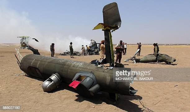 A picture taken on August 1 2016 shows Syrian rebels gathering around the wreckage of a Russian Mi8 military transport helicopter after it was shot...
