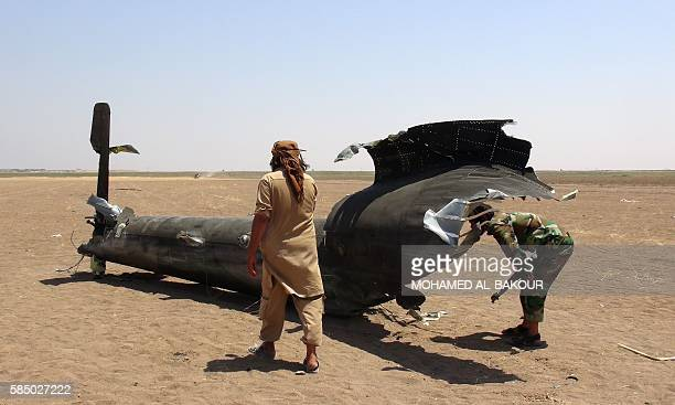 A picture taken on August 1 2016 shows Syrian rebels inspecting the wreckage of a Russian Mi8 military transport helicopter after it was shot down...