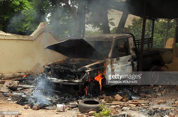 A picture taken on August 17 2016 shows the wreckage of a car burnt down during a demonstration in front of Bamako's court on August 17 2016 to...
