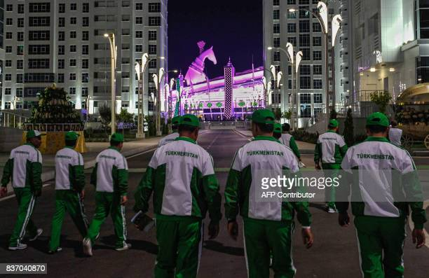 A picture taken on August 17 2017 shows men walking towards the Olympic stadium with the 4005metres tall horse head sculpture seen on top of the...