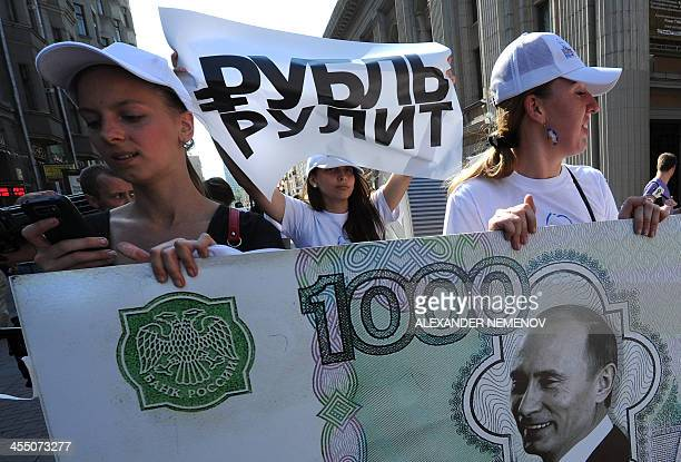 A picture taken on August 17 shows one of the members of a proVladimir Putin social network group carrying a poster with an official symbol for the...