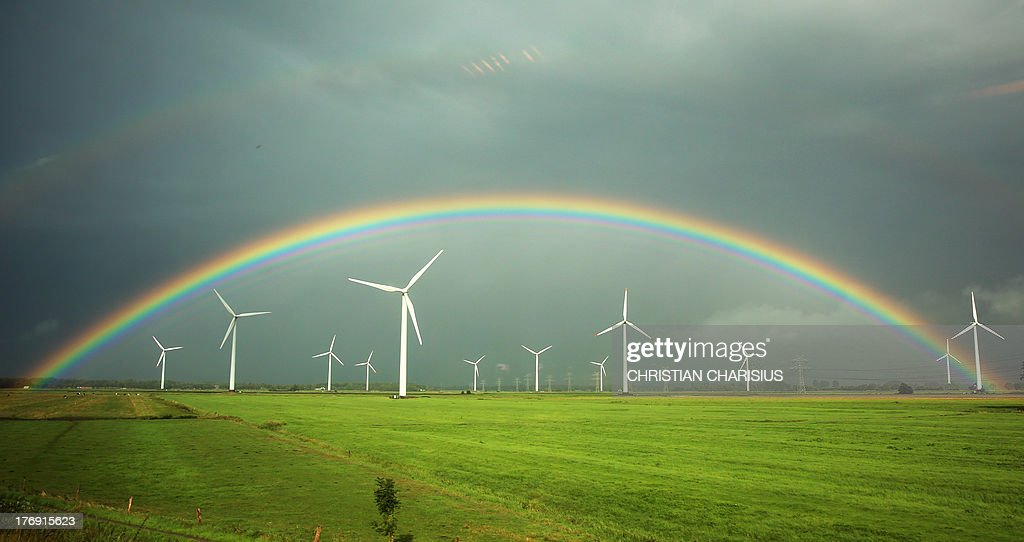 Picture taken on August 18, 2013 from a train shows a rainbow drawing over fields and wind engines near Wilster, northern Germany. AFP PHOTO / DPA / CHRISTIAN CHARISIUS / GERMANY OUT