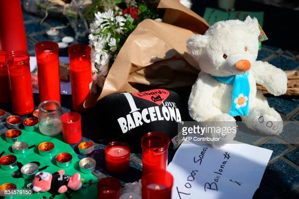 A picture taken on August 18 2017 shows flowers candles messages stuffed toys and others items displayed on the Rambla boulevard to pay tribute to...
