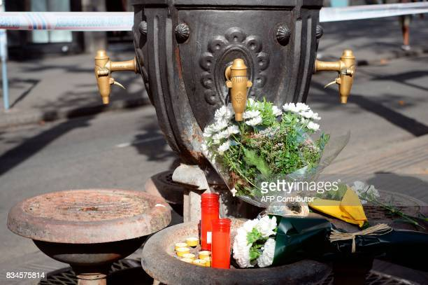 A picture taken on August 18 2017 shows flowers displayed at the Canaletas fountain on the Rambla boulevard to pay tribute to the viuctims of the...