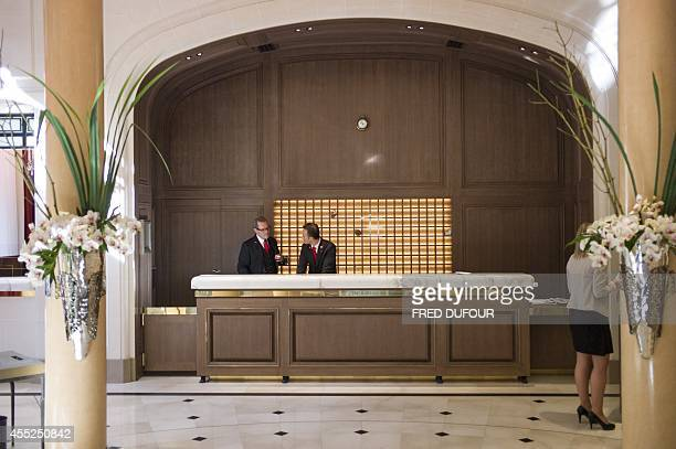 A picture taken on August 19 2014 at the Plaza Athenee hotel in Paris shows receptionists working at the lobby of the establishment The Plaza Athenee...