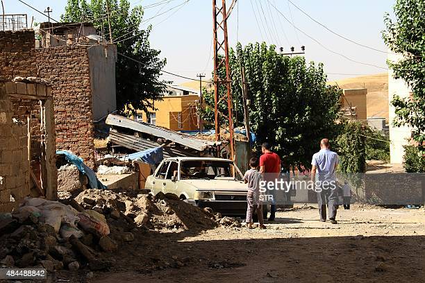 A picture taken on August 19 2015 in Diyarbakir southeast Turkey shows people walking in a street of Silvan district in Diyarbakir after clashes...