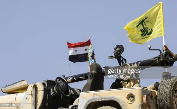 A picture taken on August 2 2017 during a tour guided by the Lebanese Shiite Hezbollah movement shows the flags of the movement and the Syrian...