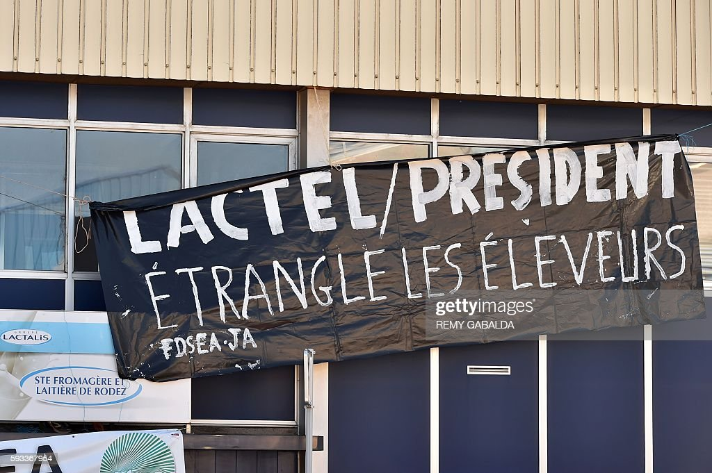 A picture taken on August 22 2016 shows a banner reading 'Lactel / President strangles the farmers' hanged on the frontage of of a factory of the...