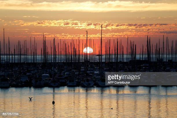 TOPSHOT A picture taken on August 22 2017 shows the sunset in the harbour of SaintMalo northwestern France / AFP PHOTO / CHARLY TRIBALLEAU