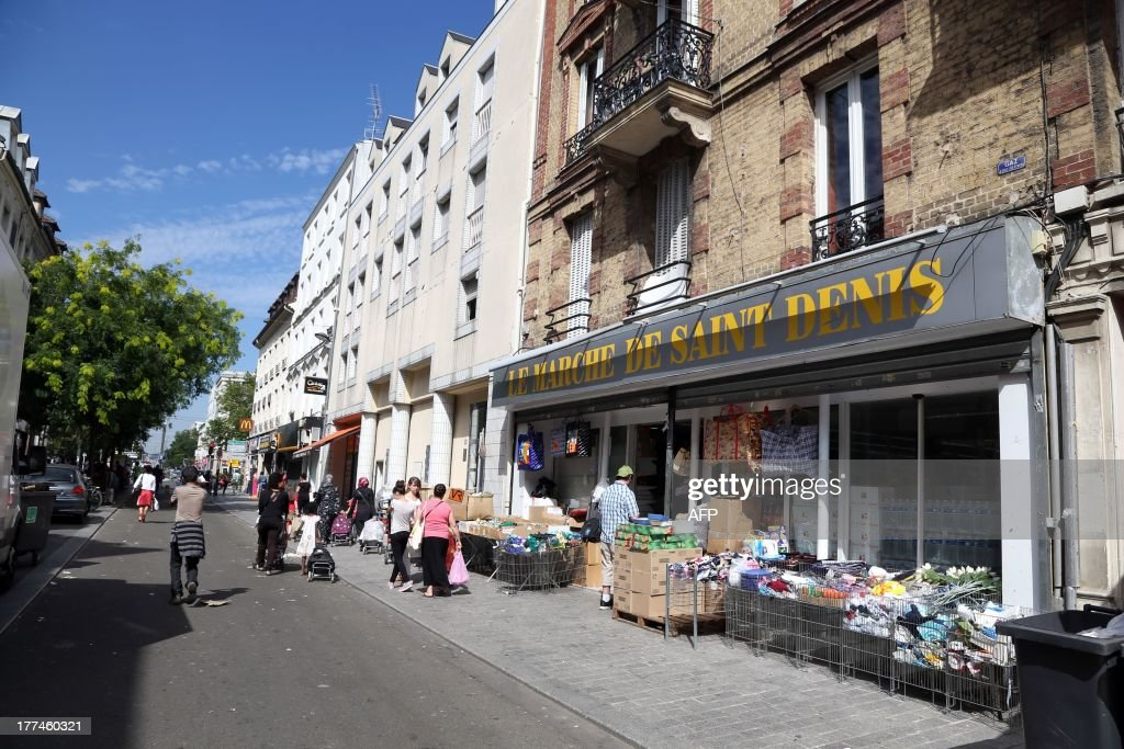 A picture taken on August 23, 2013 shows people walking down a commercial street in Saint-Denis, north of Paris. The communist city council of the city took on July 27, 2013, an executive order prohibiting for three months over 70 shops in the neighborhood near the train station from opening after 8 pm. It justified the decision stating that many shops like hair salons illegally sell alcohol in the area which is classified as a sensitive 'Zone priority security'. AFP PHOTO / THOMAS SAMSON
