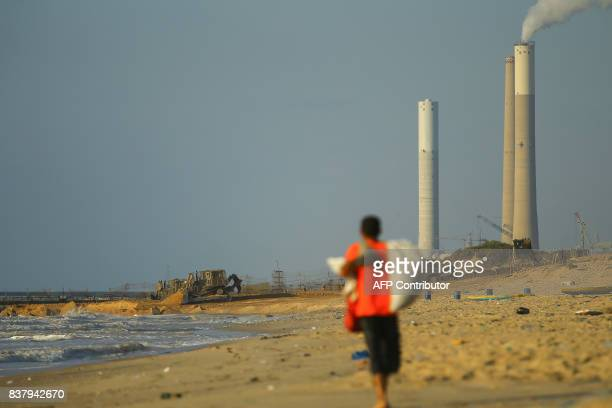 TOPSHOT A picture taken on August 23 2017 in Beit Lahia in the northern Gaza Strip shows a Palestinian walking along the beach as Israeli bulldozers...