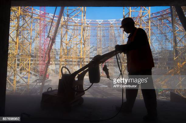 TOPSHOT A picture taken on August 23 2017 shows a worker at the Samara Arena stadium which is under construction for the upcoming 2018 FIFA World Cup...