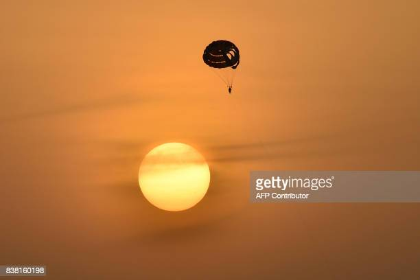 A picture taken on August 23 shows someone parasailing at sunset in Dubai / AFP PHOTO / GIUSEPPE CACACE
