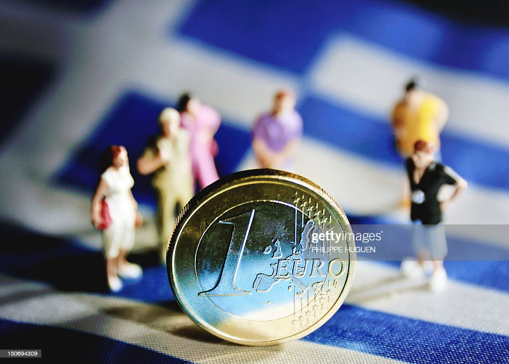 A picture taken on August 24, 2012 in Lille shows an illustration made with figurines and a euro coin set on a Greek flag. Greek Prime Minister Antonis Samaras said today that his debt-wracked country was not asking for more cash to solve its problems, but required more 'breathing space' to carry out cuts and reforms. Greece is bound under its loan agreement with the EU and the IMF to bring its public deficit to below 3.0 percent of output by 2014 to continue receiving bankruptcy-saving funds.