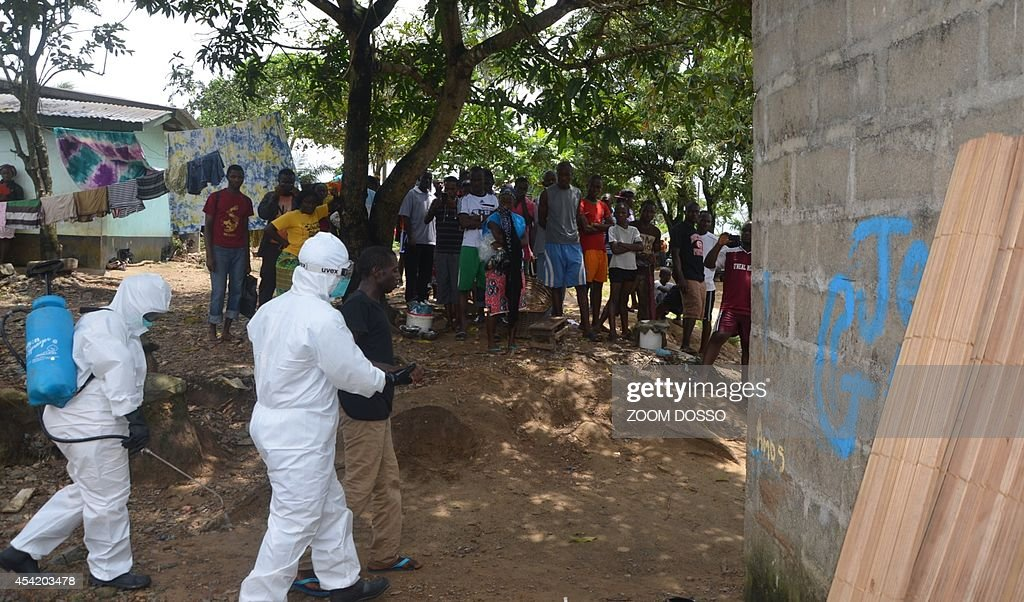 A picture taken on August 25, 2014 in Monrovia shows nurses wearing a protective suit escorting a man infected with the Ebola virus to a hospital in Monrovia. The United Nations vowed on August 23 to play a 'strong role' in helping Liberia and its neighbours fight a deadly outbreak of Ebola in west Africa, which it said could take months to bring it under control. Liberia has been particularly hard hit by the epidemic that has swept relentlessly across the region since March, accounting for almost half of the 1,427 deaths.