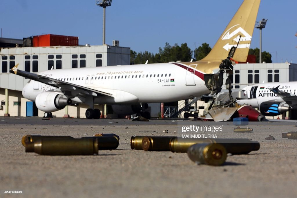 A picture taken on August 26 shows bullet casing and damaged airplanes on the tarmac at Tripoli international airport in the Libyan capital after...