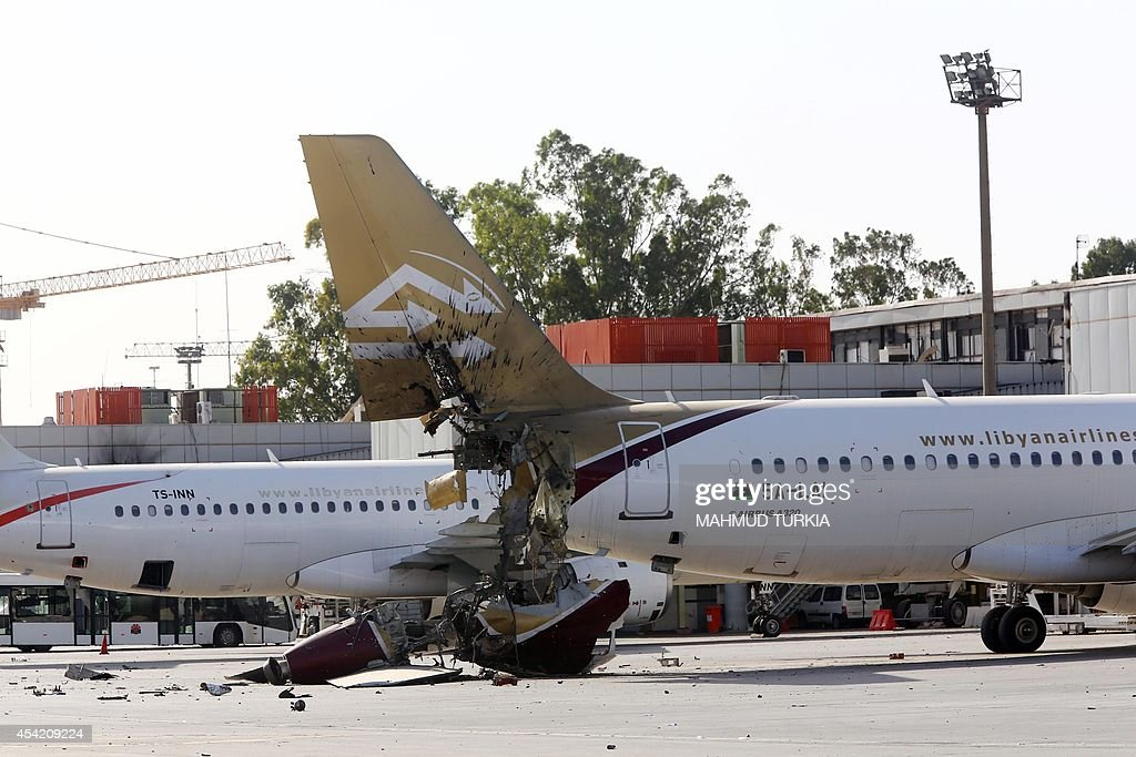 A picture taken on August 26 shows damaged airplanes on the tarmac at Tripoli international airport in the Libyan capital after fighters from the...