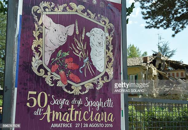 A picture taken on August 27 2016 shows a poster of the 50th Spaghetti all'Amatriciana Festival next to a damaged building in the Italian village of...