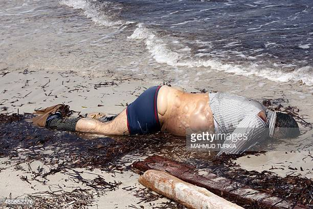 A picture taken on August 28 2015 shows the body of a migrant that had washed ashore on a beach in the port town of Zuwara about 160 kms West of...