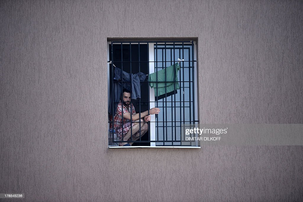 A picture taken on August 28, 2013, shows a refugee man behind a barred window at Bulgaria's shelter for clandestine migrants near Lyubimets, as the small EU state finds it hard to cope with an ever rising number of Syrians fleeing conflict at home. Over 3,100 clandestine migrants -- half of them Syrians -- have crossed into Bulgaria from neighbouring Turkey this year, doubling their numbers compared to 2012 and and causing Bulgaria's few temporary accommodation facilities to overflow. STORY by Vessela SERGUEVA