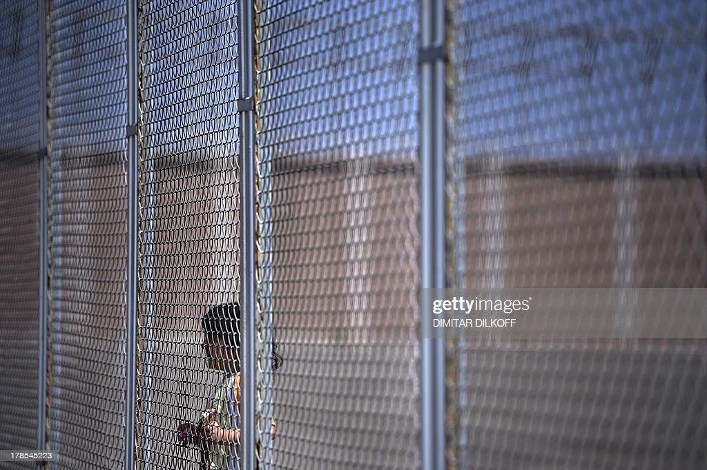 A picture taken on August 28, 2013, shows a Syrian girl behind a fence at Bulgaria's shelter for clandestine migrants near Lyubimets, as the small EU state finds it hard to cope with an ever rising number of Syrians fleeing conflict at home. Over 3,100 clandestine migrants -- half of them Syrians -- have crossed into Bulgaria from neighbouring Turkey this year, doubling their numbers compared to 2012 and and causing Bulgaria's few temporary accommodation facilities to overflow. STORY by Vessela SERGUEVA