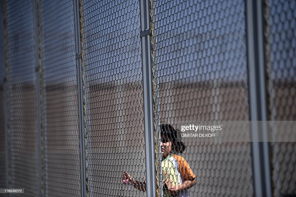 A picture taken on August 28, 2013, shows a Syrian girl behind a fence at Bulgaria's shelter for clandestine migrants near Lyubimets, as the small EU state finds it hard to cope with an ever rising number of Syrians fleeing conflict at home. Over 3,100 clandestine migrants -- half of them Syrians -- have crossed into Bulgaria from neighbouring Turkey this year, doubling their numbers compared to 2012 and and causing Bulgaria's few temporary accommodation facilities to overflow. AFP PHOTO / DIMITAR DILKOFF STORY by Vessela SERGUEVA