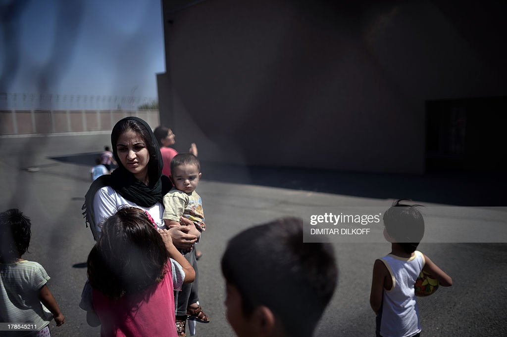 A picture taken on August 28, 2013, shows a Syrian woman carrying her child behind a fence at Bulgaria's shelter for clandestine migrants near Lyubimets, as the small EU state finds it hard to cope with an ever rising number of Syrians fleeing conflict at home. Over 3,100 clandestine migrants -- half of them Syrians -- have crossed into Bulgaria from neighbouring Turkey this year, doubling their numbers compared to 2012 and and causing Bulgaria's few temporary accommodation facilities to overflow. AFP PHOTO / DIMITAR DILKOFF STORY by Vessela SERGUEVA