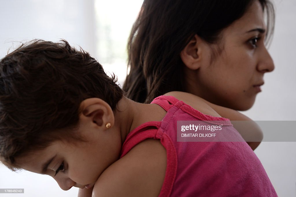 A picture taken on August 28, 2013, shows Janda Hussein, a 29-year-old woman from Damascus carrying her two-year-old daughter at Bulgaria's shelter for clandestine migrants near Lyubimets, as the small EU state finds it hard to cope with an ever rising number of Syrians fleeing conflict at home. Over 3,100 clandestine migrants -- half of them Syrians -- have crossed into Bulgaria from neighbouring Turkey this year, doubling their numbers compared to 2012 and and causing Bulgaria's few temporary accommodation facilities to overflow. STORY by Vessela SERGUEVA